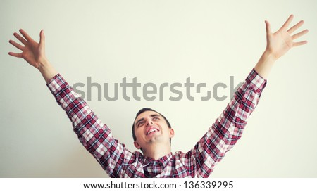 happy young male with his arms up in victory gesture - stock photo