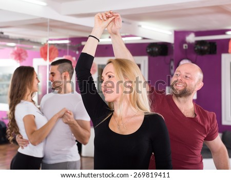 Happy young males and females  having dancing class indoors - stock photo