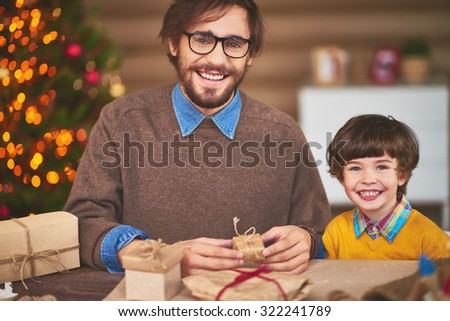 Happy young man and his son preparing Christmas surprises for friends - stock photo