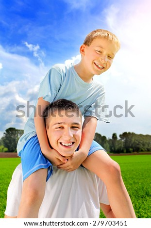 Happy young man and Kid in the summer field - stock photo