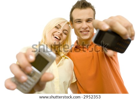 Happy young man and woman are showing mobile's screen to the camera. Isolated on white background in studio. - stock photo