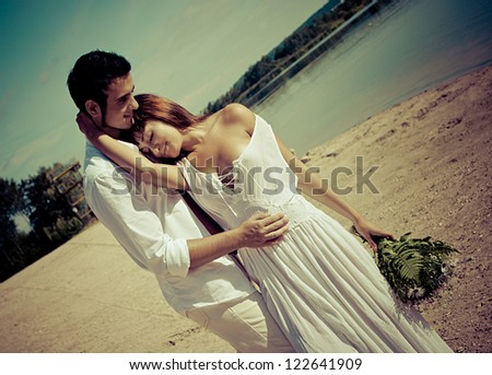 Happy young man and woman couple in a beach - stock photo