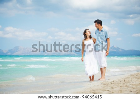 Happy young man and woman couple walking, laughing and holding hands on a deserted tropical beach with bright clear blue sky - stock photo