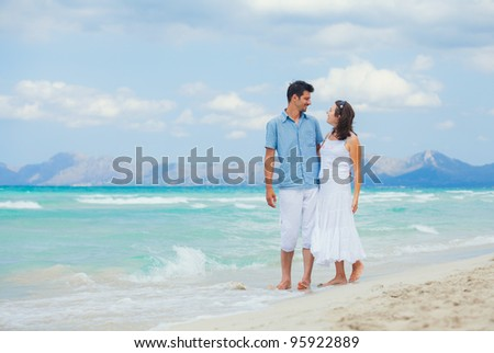 Happy young man and woman couple walking, laughing and holding hands on a deserted tropical beach with bright clear blue sky
