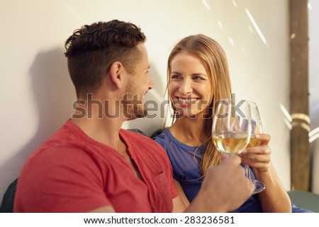 Happy young man and woman enjoying a glass of wine in their backyard. Couple toasting wine and looking at each other smiling. - stock photo