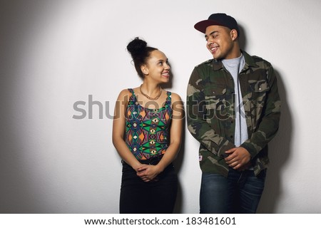 Happy young man and woman looking at each other smiling. Young couple in love against grey background. - stock photo