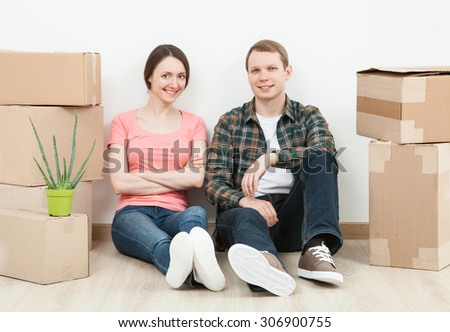 Happy young man and woman sitting near  cardboard boxes, neutral background - stock photo