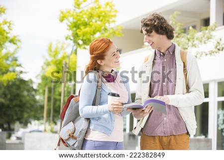 Happy young man and woman studying together at college campus - stock photo