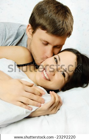 happy young man and woman wake up in the morning  in bed and kiss