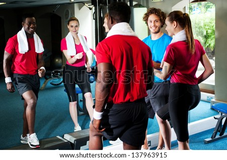 Happy young man and woman with fitness trainer in a gym.