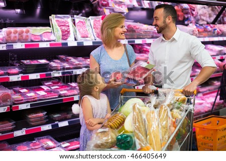 Happy young man and woman with girl choosing meat in food store