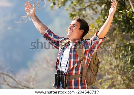 happy young man arms open on top of the mountain - stock photo