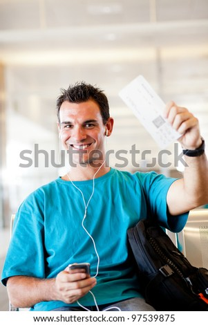 happy young man at airport with boarding pass - stock photo