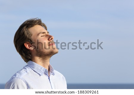 Happy young man breathing deep with the horizon in the background - stock photo