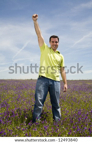Happy young man celebrating success in a spring field - stock photo