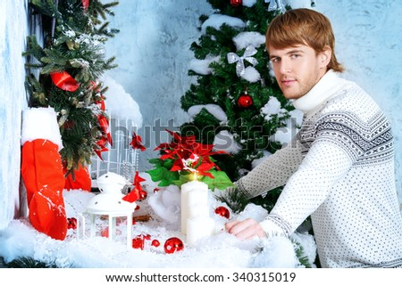 Happy young man celebrating winter holidays at home beautifully decorated for Christmas.  - stock photo