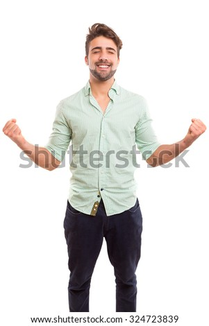 Happy young man celebrating with arms open - stock photo