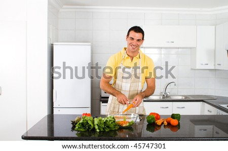 happy young man cutting vegetables in kitchen - stock photo