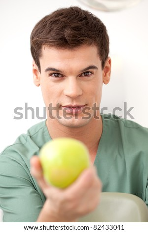 Happy young man dentist holding an apple out to the camera