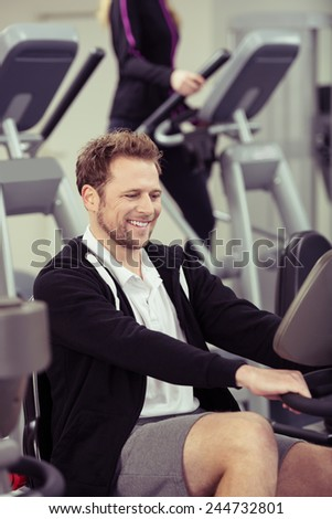 Happy young man exercising on gym equipment smiling as he keeps a close watch on his performance on the monitor in a health and fitness concept - stock photo