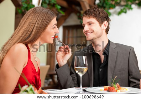 Happy young man feeding woman at the restaurant table - stock photo