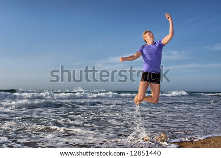 Happy young man flies with mobile phone on beach. Shot in Sodwana Bay Nature Reserve, KwaZulu-Natal province, Southern Mozambique area, South Africa.