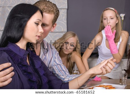 Happy young man gifting a ring to a beautiful surprised young woman surrounded by her envy friends in their apartment. - stock photo