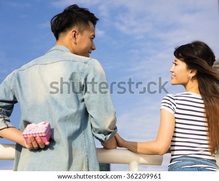 happy young man gives a gift to  girlfriend - stock photo