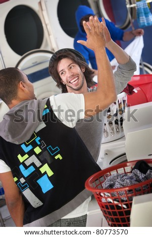 Happy young man gives high five to his friend in a Laundromat - stock photo