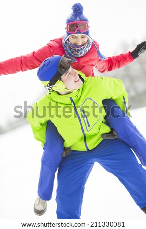 Happy young man giving piggyback ride to woman in snow - stock photo