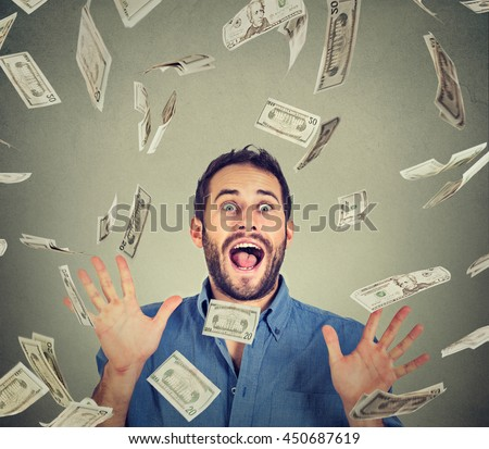 Happy young man going crazy screaming super excited. Portrait ecstatic guy celebrates success under money rain falling down dollar bills banknotes isolated gray background. Financial freedom concept - stock photo