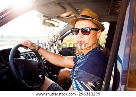 Happy young man going on holidays with friends,in a open top car.Loving couple enjoying on a road trip.Handsome man driving car on road,opposite the sunset,muscular man,hat,sunglasses,vintage style - stock photo