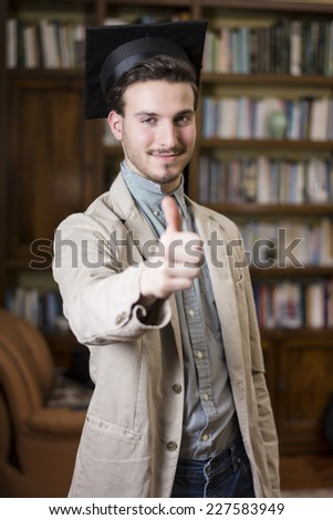 Happy young man graduating from college, with graduation hat, doing thumb up sign - stock photo