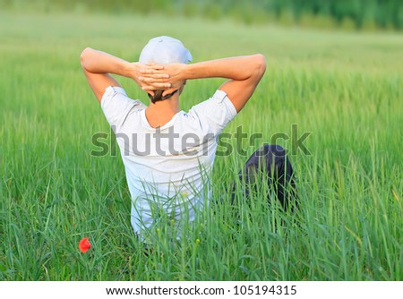 Happy young man have a rest on a nature field - stock photo