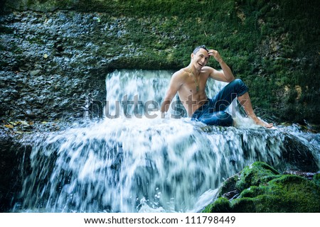 Happy young man having fun and relax under waterfall.