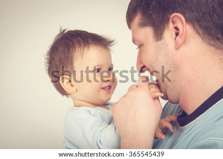 Happy young man holding a smiling baby. Father and son - stock photo