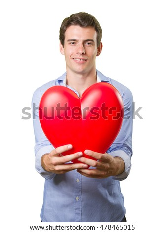 Happy young man holding a toy heart on white background