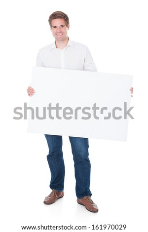 Happy Young Man Holding Blank Placard Over White Background - stock photo