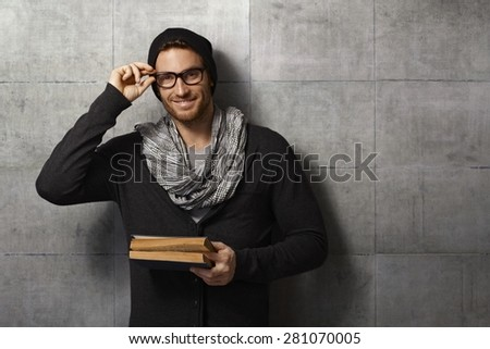 Happy, young man holding book, looking at camera, leaning against grey wall. - stock photo