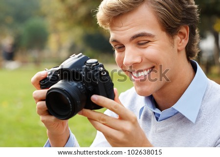 Happy  young man holding camera taking photos is photographer - stock photo