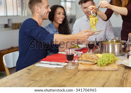 Happy Young Man Holding his Plate While Someone is Dishing Up for Him During Dinner. - stock photo