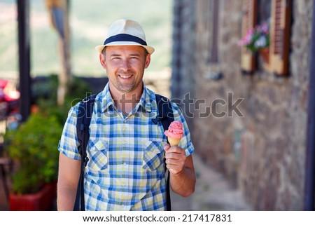Happy young man holding ice cream - stock photo