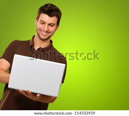 Happy Young Man Holding Laptop On Green Background
