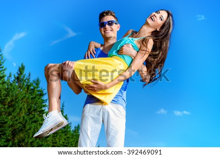 Happy young man holding on hands his girlfriend. Happy summer day.  - stock photo