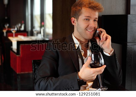 Happy young man in a black suit at a restaurant talking on the phone - stock photo