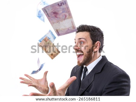 Happy young man in a rain of Brazilian Money - stock photo