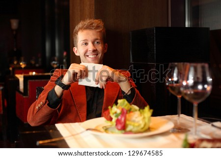 Happy young man in a red suit holding a napkin - stock photo