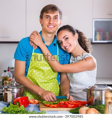 Happy young man in apron helping smiling wife to prepare healthy dinner