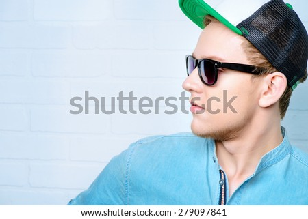 Happy young man in casual clothes and sunglasses posing at studio.  - stock photo