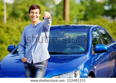 Happy young man in glasses standing in front of his new car and showing car key - stock photo